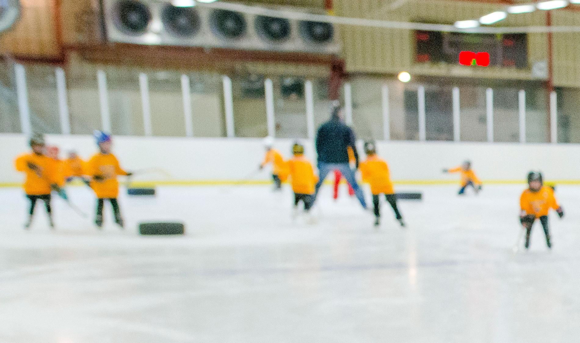 Barn spelar ishockey. Arkivbild