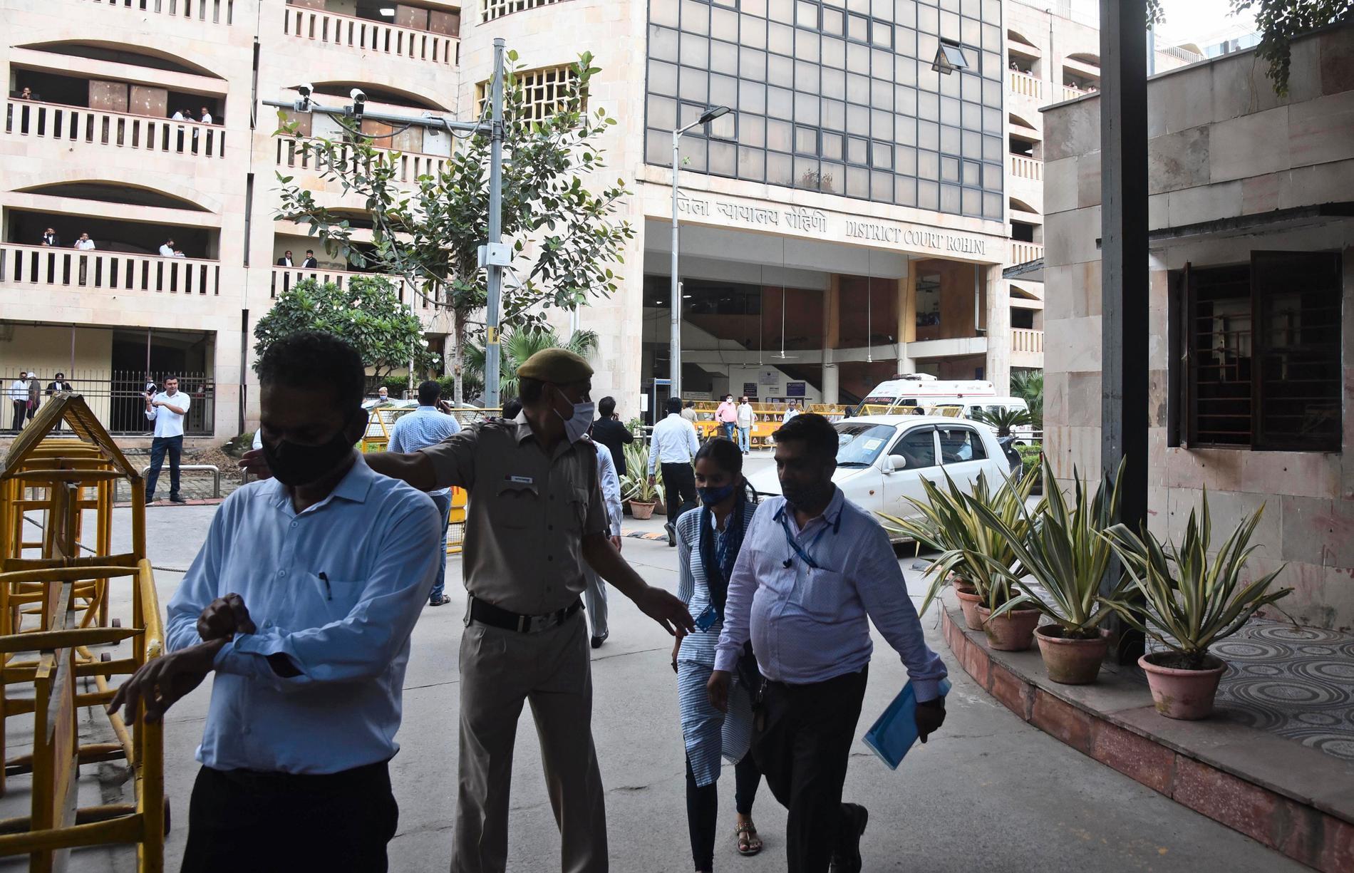 En misstänkt gängledare sköts till döds av två lönnmördare som var utklädda till advokater i en rättssal under fredagen.