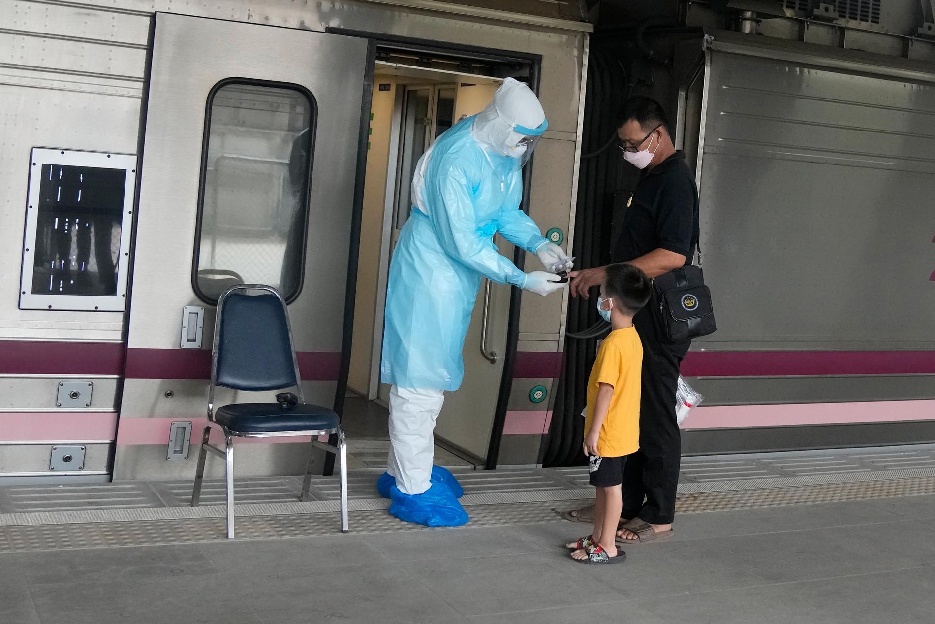 En sjukvårdare testar syrenivåerna på en covidsmittad som ska åka med tåg från Bangkok till sin hemstad. Syftet är att minska trycket på sjukvården i huvudstaden.