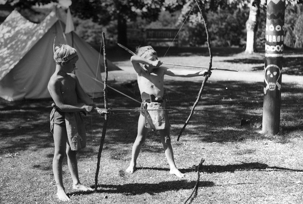 Prins Carl Gustaf och hans kompis leker med pilbågar.
