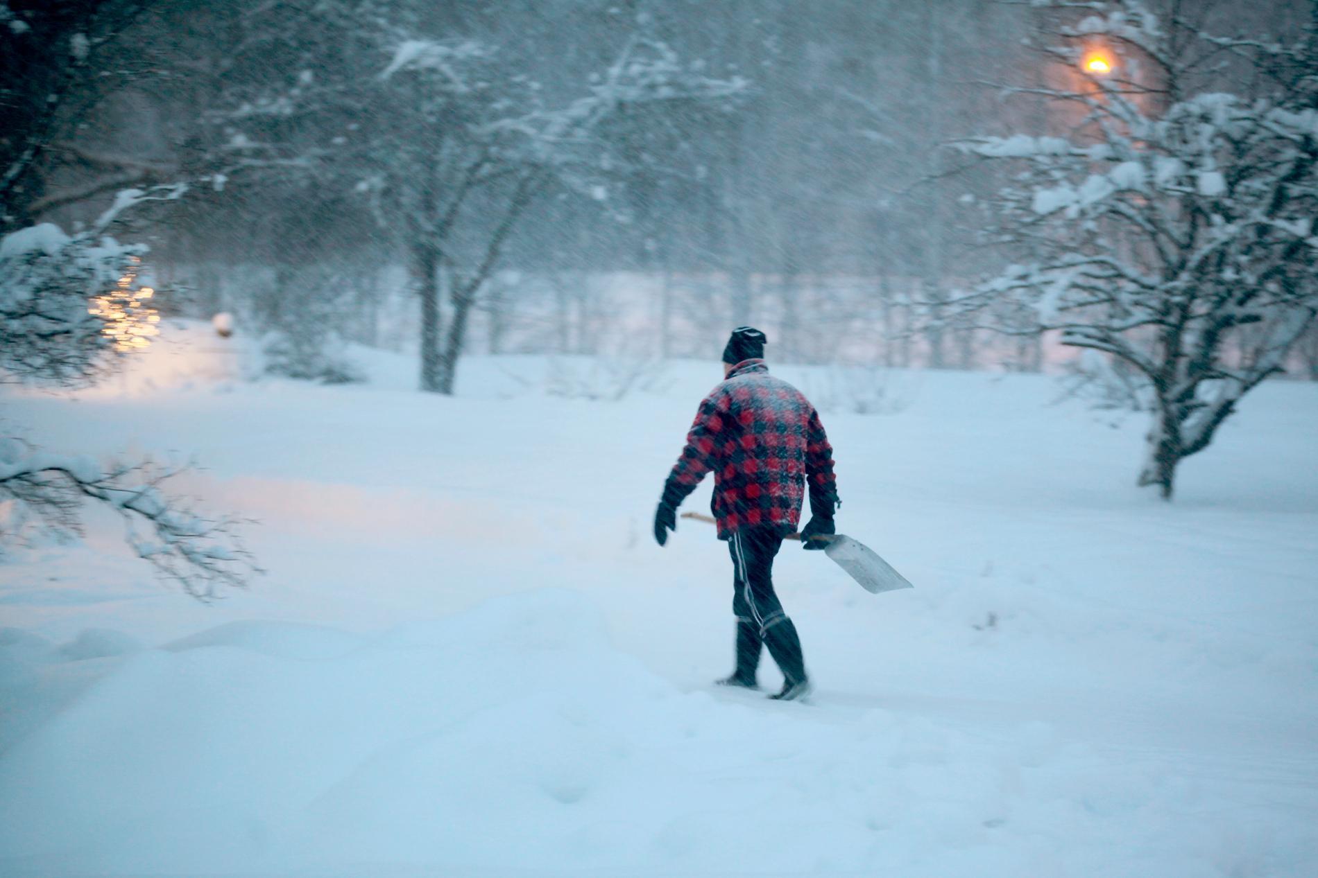 En man är ute för att skotta snö i Sundsvall.