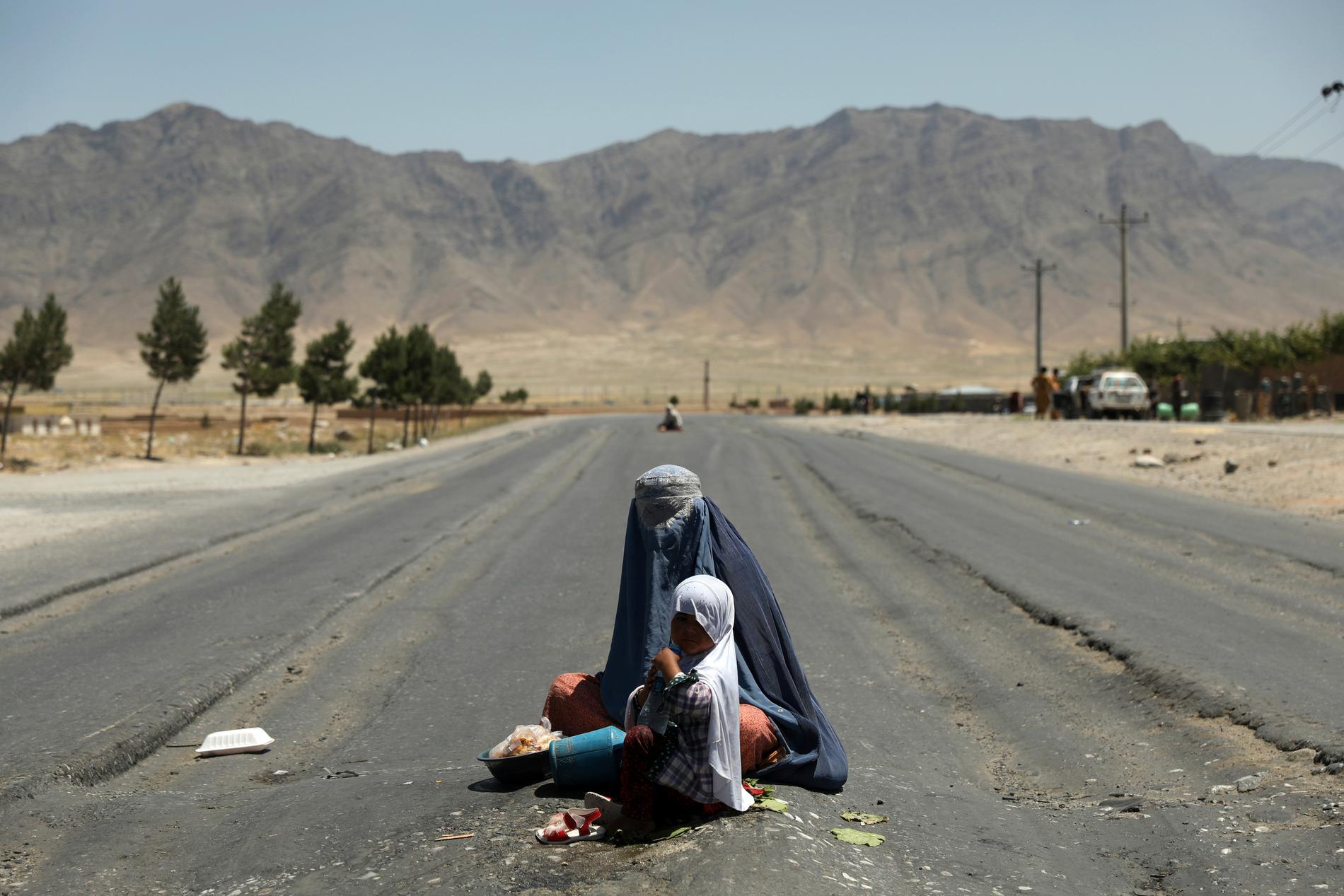En afghansk kvinna tigger på motorvägen mot Bagram, norr om Kabul.