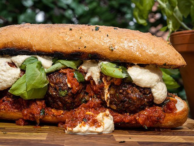 Köttbullsmacka med tomat och ostsås tillsammans med läckert vitlöksbröd.