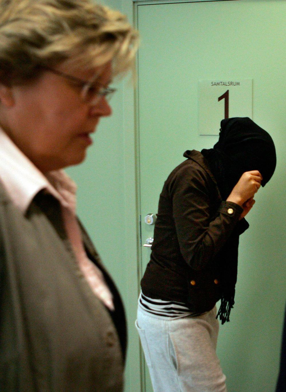 En av medlemmarna i Tjejligan döljer sitt ansikte på väg in i rättegångssalen vid Solna tingsrätt.