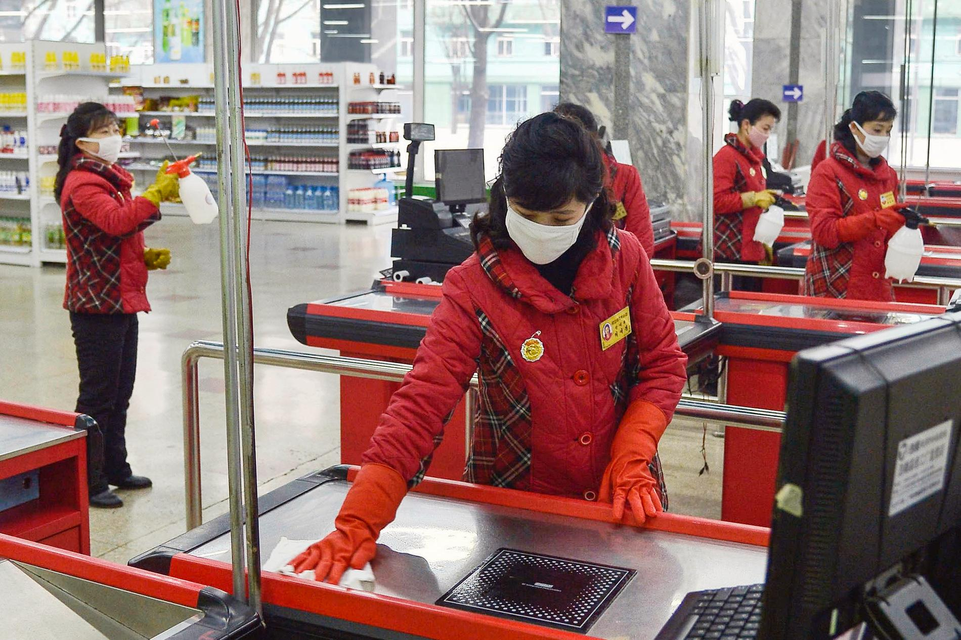 Anställda desinficerar en butik i Pyongyang.