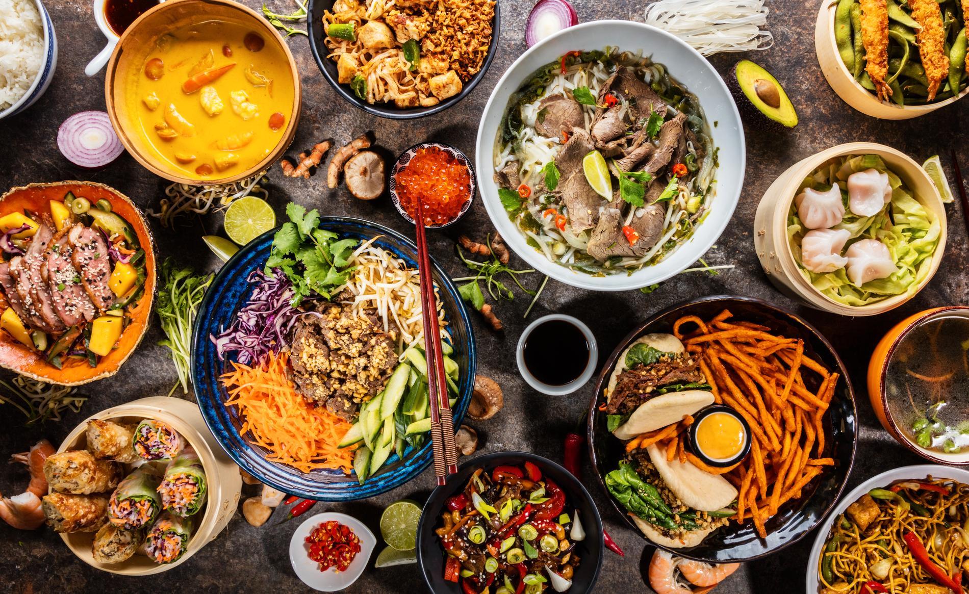 Olika asiatiska maträtter i skålar ovanifrån