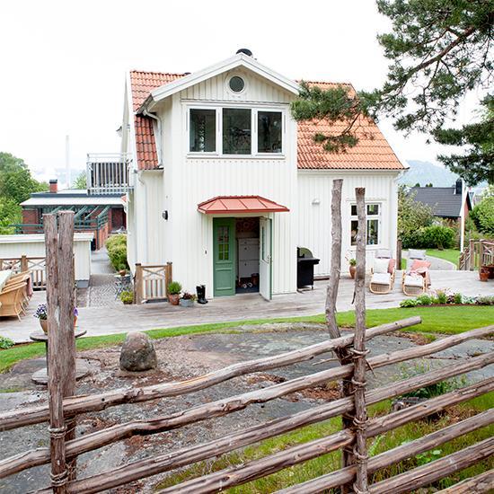 """Familjens vita villa omges av en stilig gärdesgård signerad Öjerssons staket i Kungsbacka. """"Gärdesgården anlades förra året och är ett riktigt hantverk! Det är inte många som är utbildade och kan anlägga dem i Sverige i dag. Det var ett års väntetid innan vi fick vår"""", berättar Victoria."""