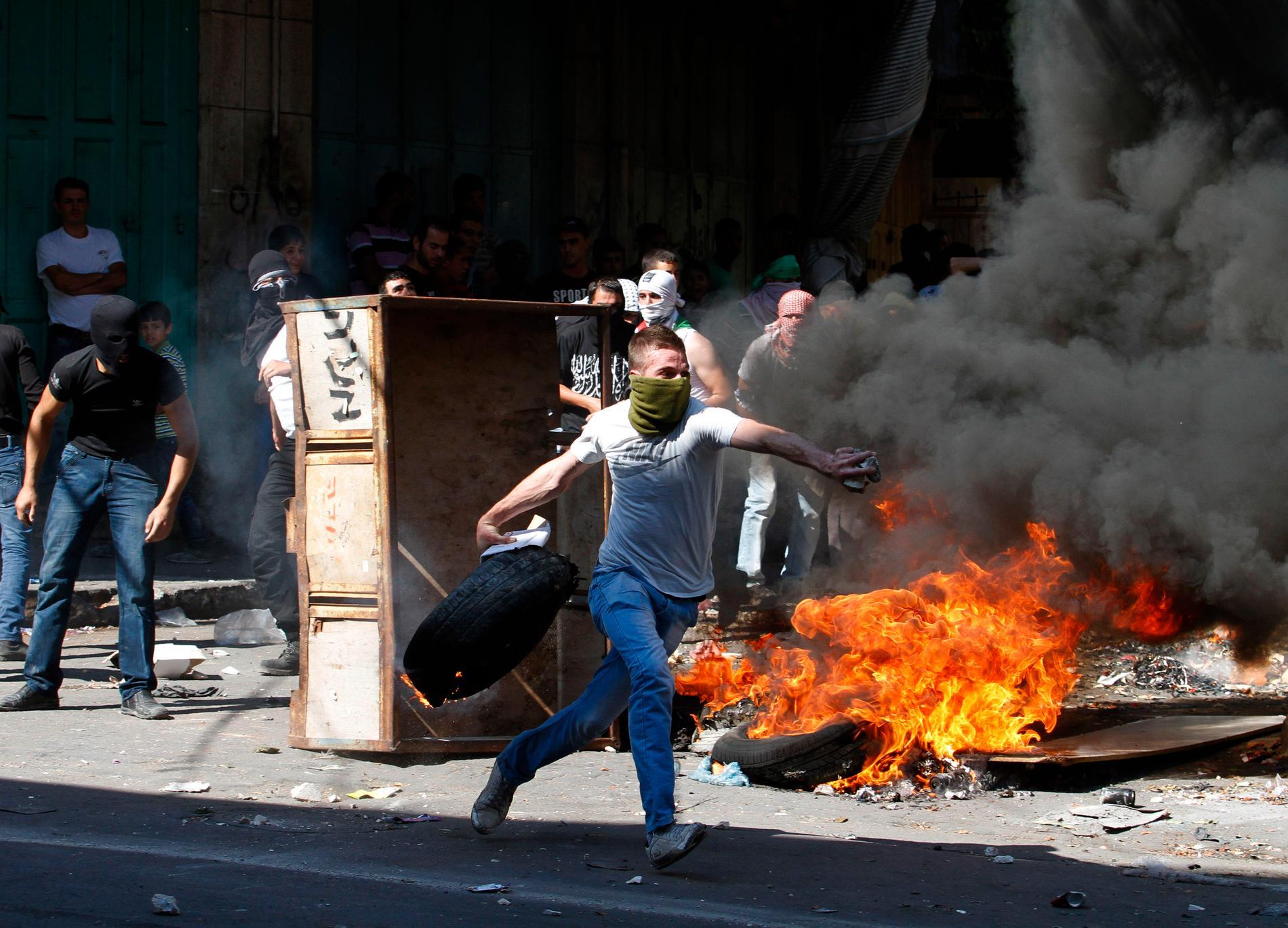 En ung palestinier kastar ett bildäck mot en isralisk polis.