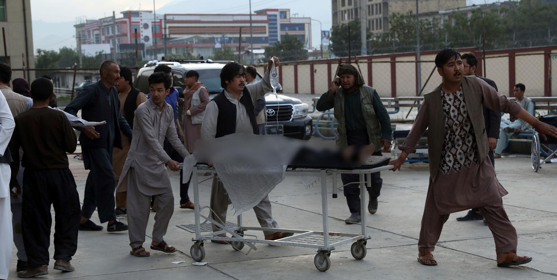 En skadad skolelev transporteras till sjukhus efter bombexplosionen nära en skola i Kabul lördagen den 8 maj. Enligt Afghanistans regering är offren övervägande unga kvinnliga studenter.