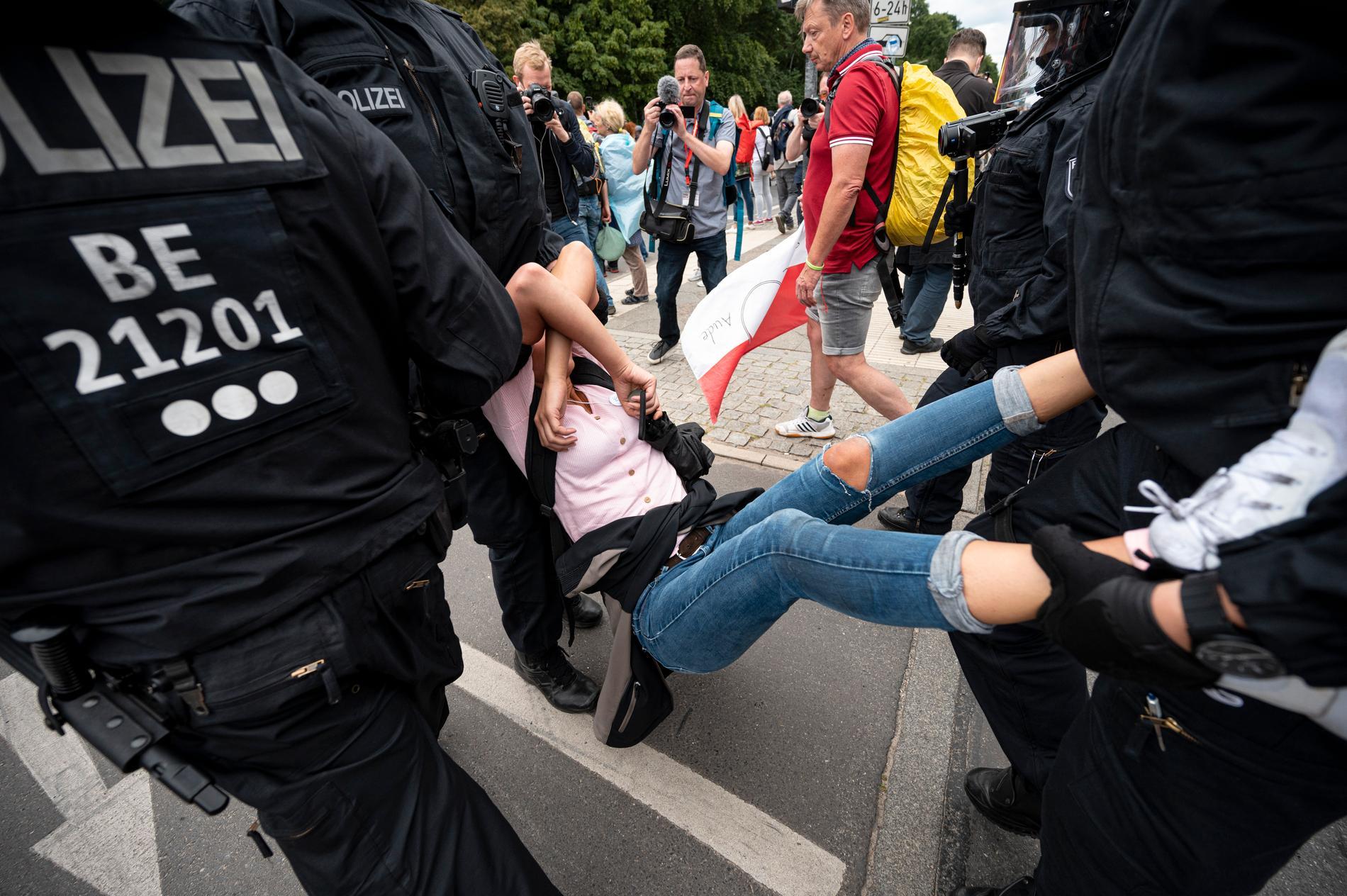 Polis griper en deltagare i den olagliga demonstrationen mot Tysklands coronaregler i Berlin på söndagen.