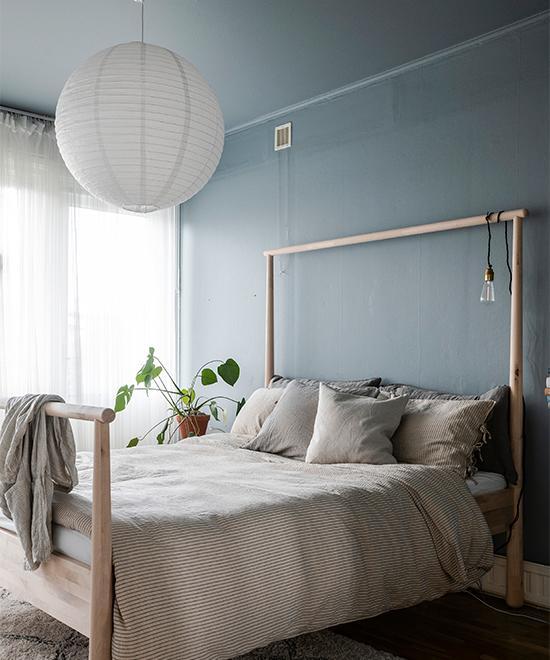 Josefines sovrum går i blågrå toner, där såväl väggar som tak är målade i kulören NCS S 4010-B10G, även kallad Linblå, från Jotun. Sänggavel från Ikea.