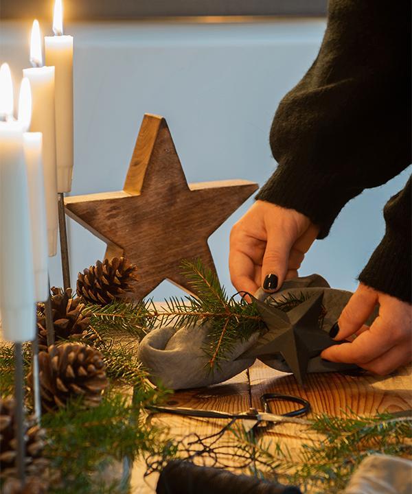 Amanda förbereder för juldukningen. Träljusstaken har Amanda gjort av en gammal bräda och några rostiga spikar. Även här en enkel dekoration med kottar och gran.