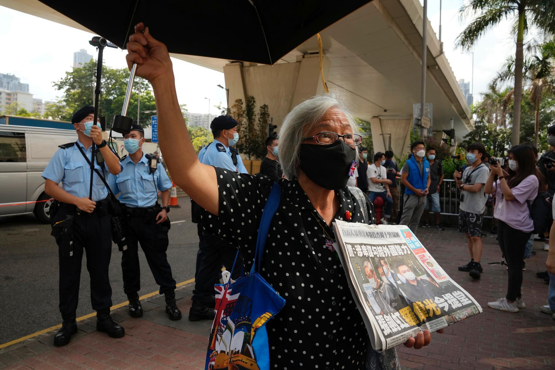 Demonstranter protesterar utanför domstolen i Hongkong till stöd för två chefer vid den prodemokratiska tidningen Apple Daily.