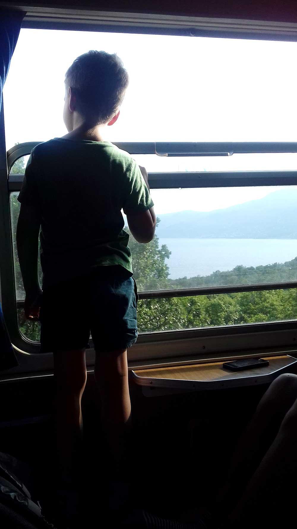 Olof, 7 år, kikar ut över landskapet som far förbi.