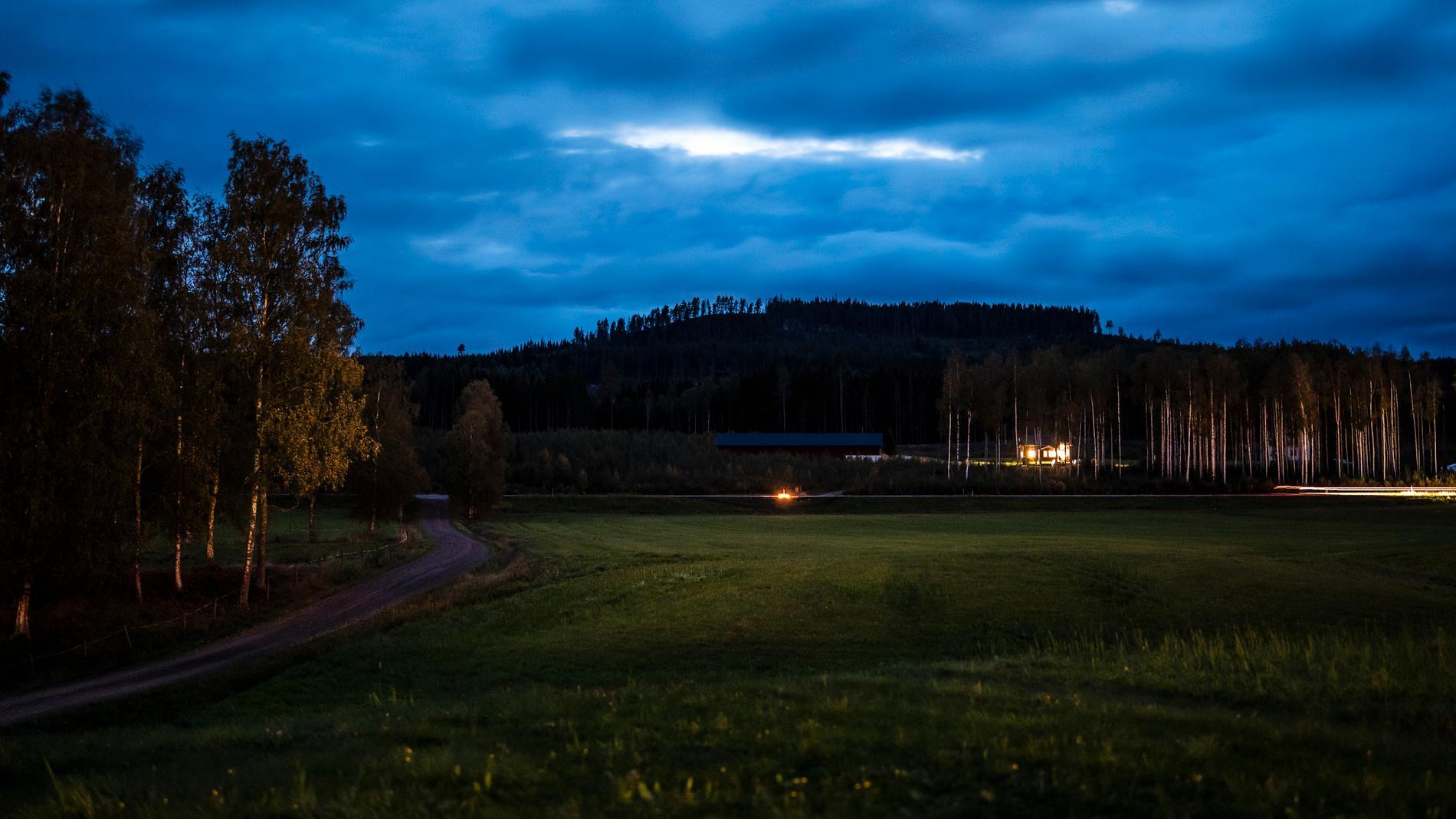 Tända ljus för de omkomna lyser upp vägsträckan under söndagskvällen.