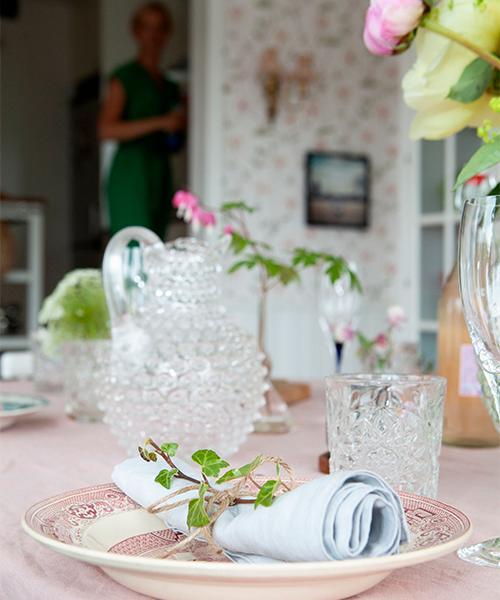 Rosa linneduk från H&M home och karaff från Artilleriet. Glas från Åhléns och vinglas från Orrefors. På servetten ligger murgröna från egna trädgården.