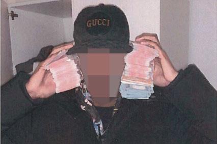 Den åtalade 22-åringen poserar med rejäla sedelbuntar. Enligt utredningen togs bilden, som hämtats från en telefon, i nära anslutning till ett av bedrägerisamtalen.