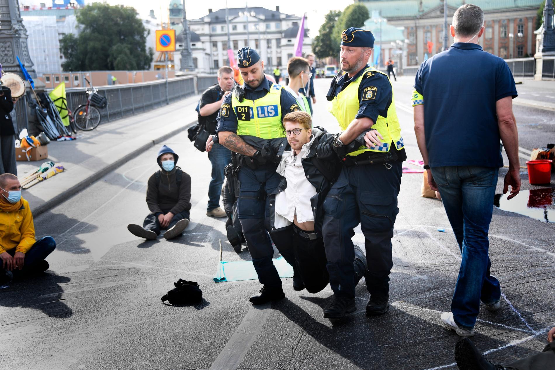 Polisen avlägsnar demonstranter på Vasabron i Stockholm.