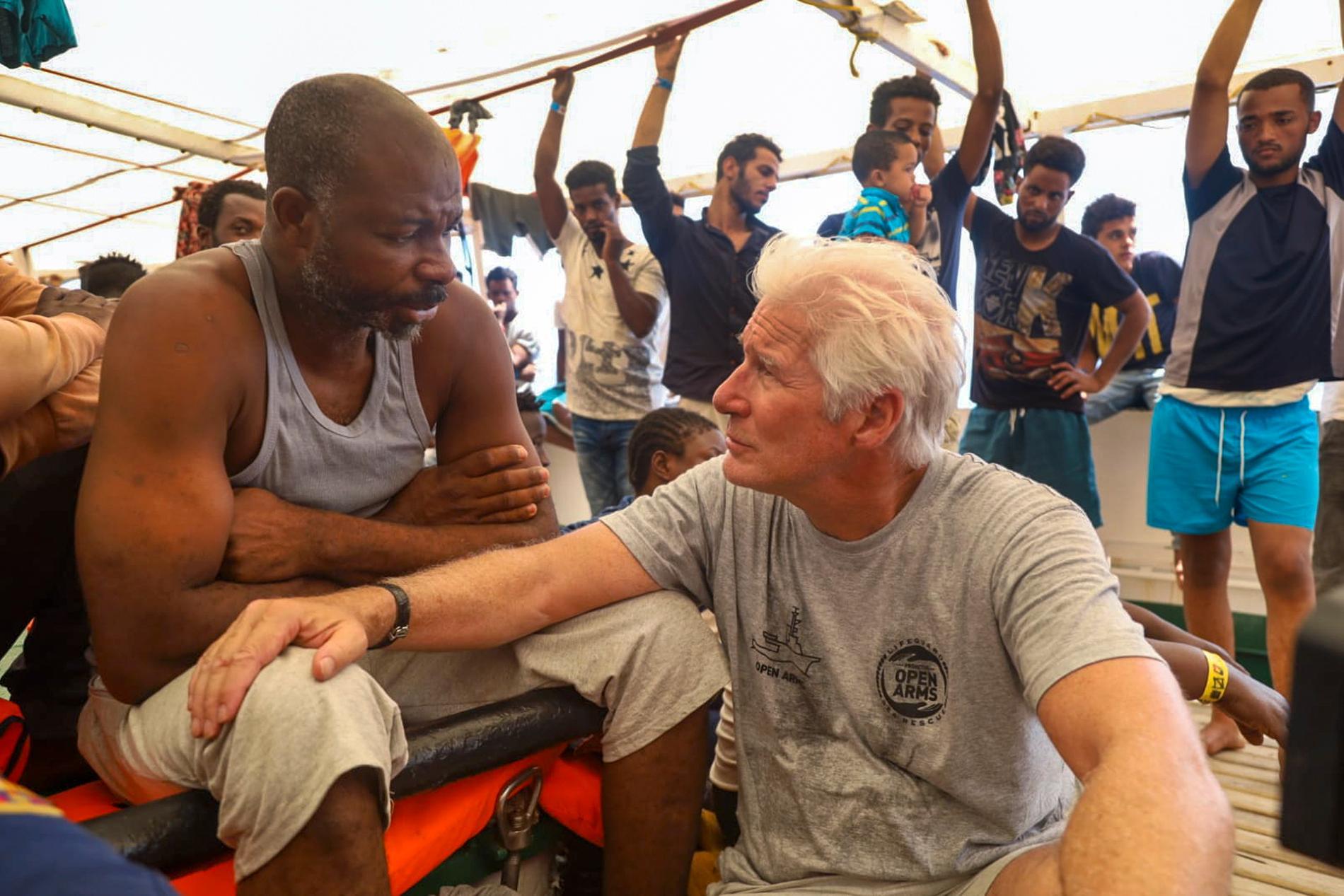 Skådespelaren Richard Gere pratar med en migrant ombord fartyget Open Arms 2019.