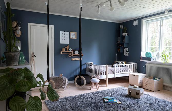 Gideons rum går i mörkblått. Sängen kommer från Oliverfurniture, mattan från Mio. Ringarna i taket är köpta på Decathlon.