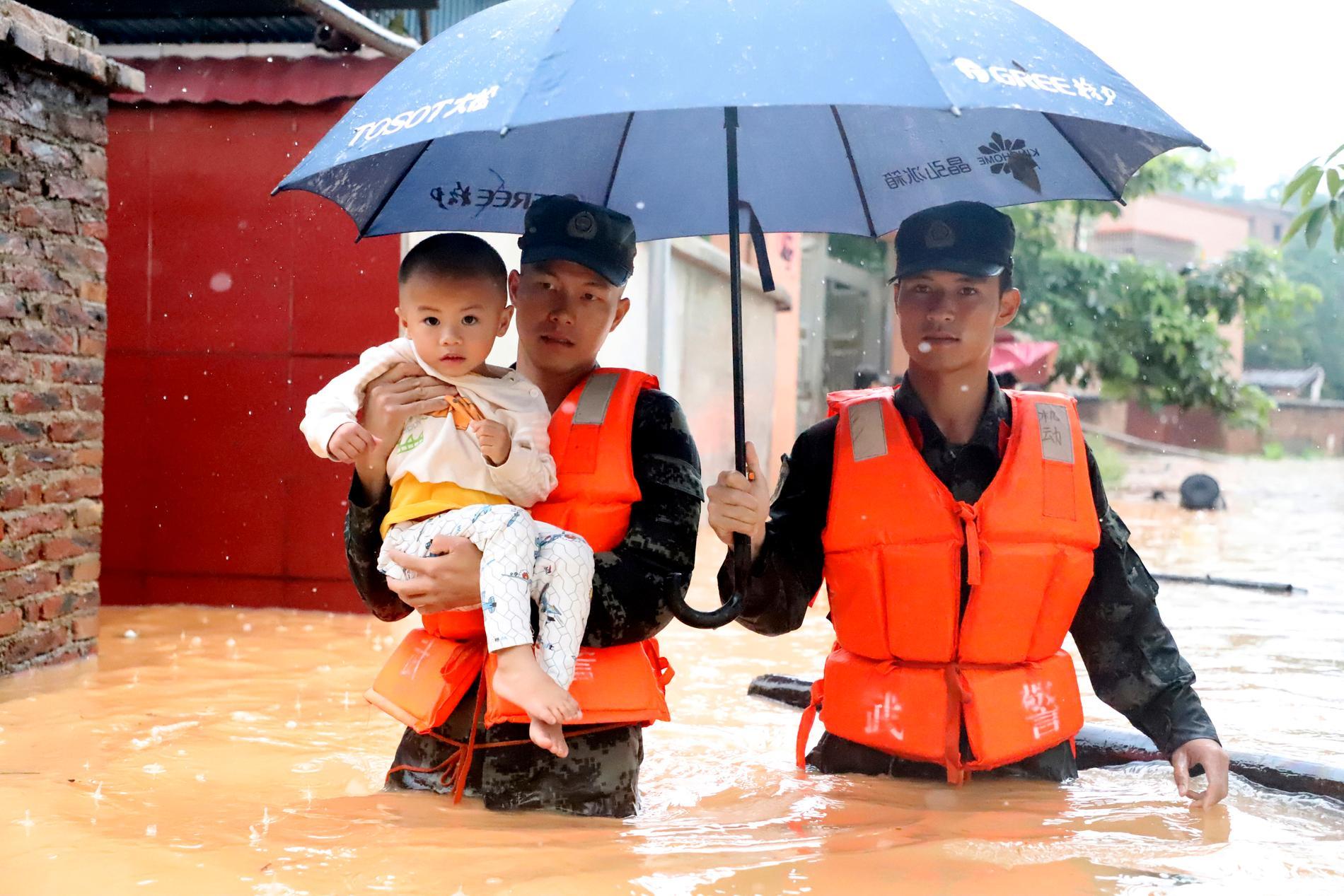 Ett barn evakueras tidigare i veckan i den översvämmade byn Qingyuan i Guangdong-provinsen i södra Kina.
