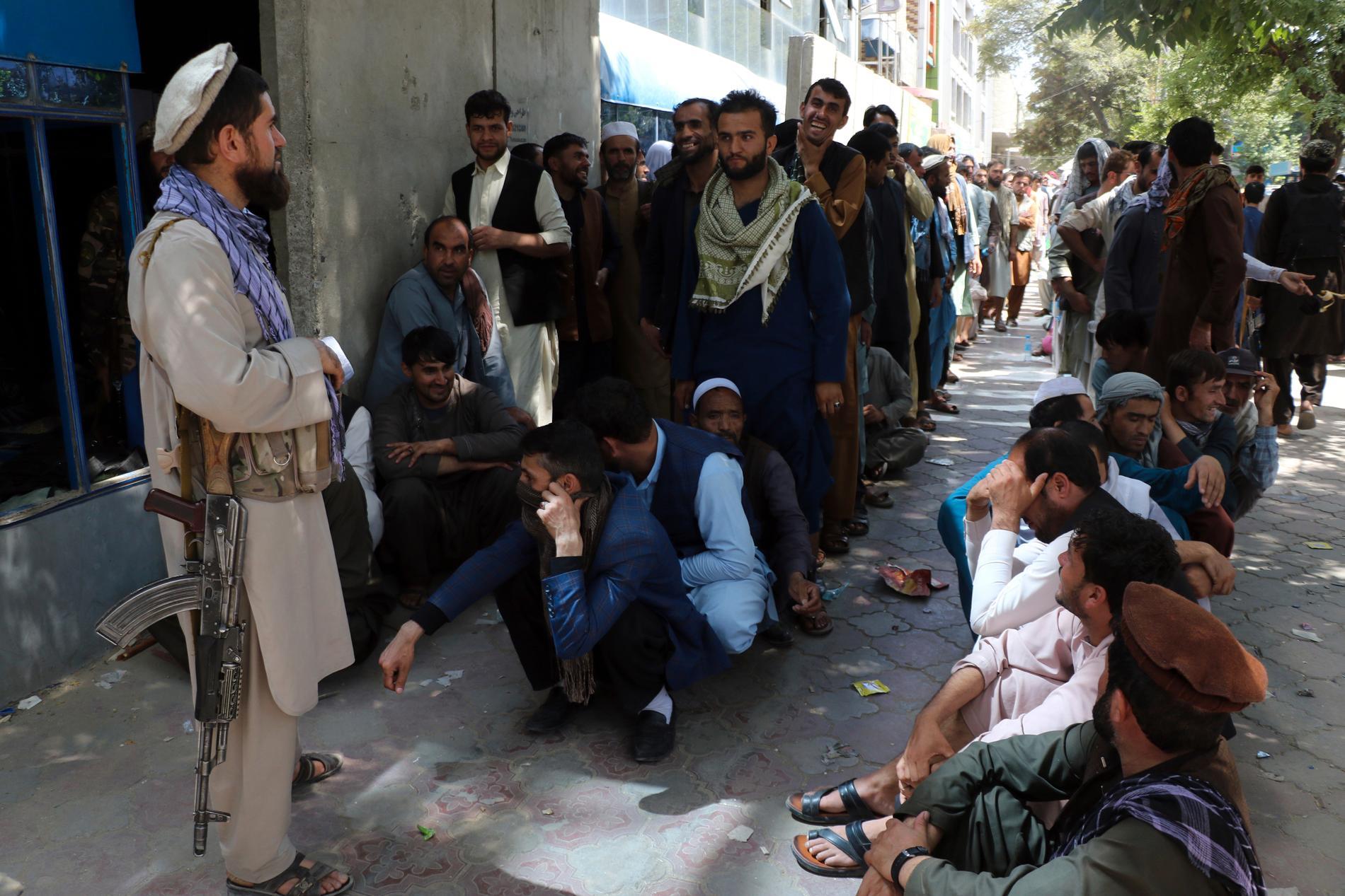En taliban bevakar en kö framför en bank i den afghanska huvudstaden.