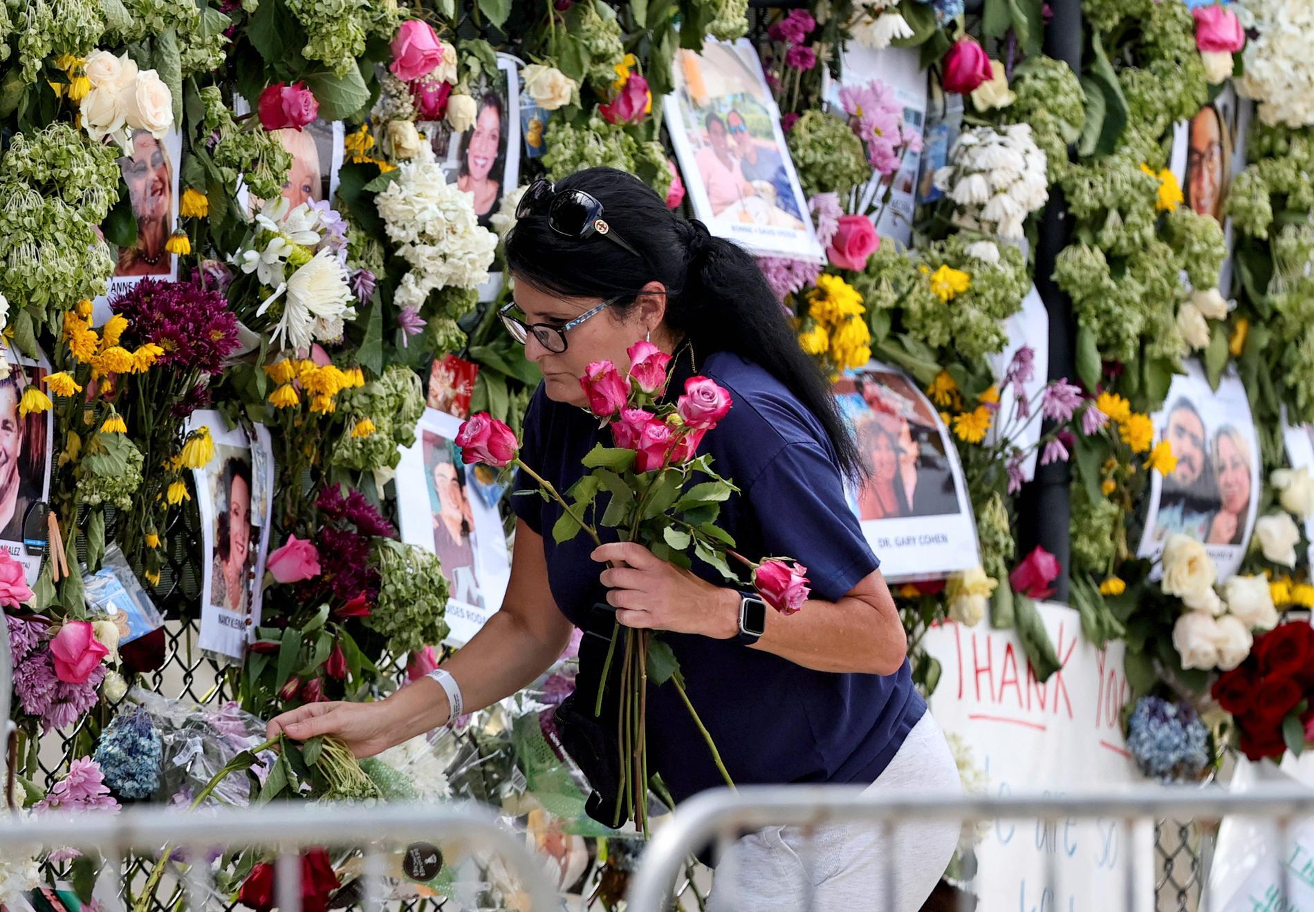 En kvinna lämnar blommor vid en minnesplats i Miami.