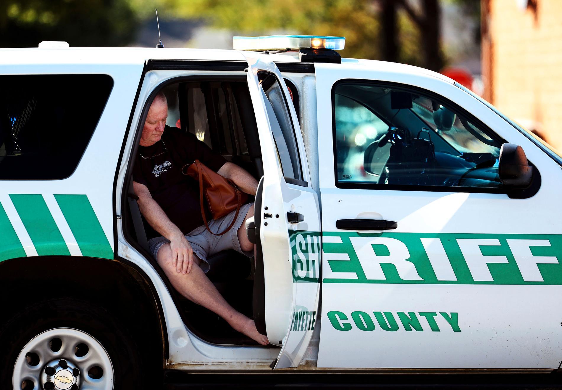En man vilar ut i en polisbil efter skjutningen.
