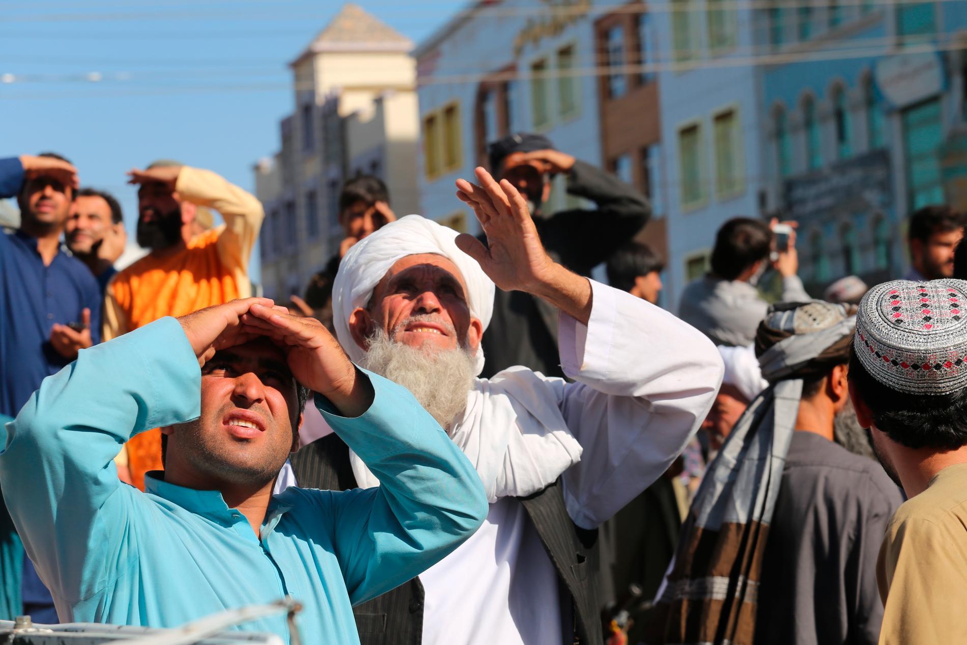 Människor ser på när talibaner hissar en död kropp i en kran över huvudtorget i staden Herat i Afghanistan.