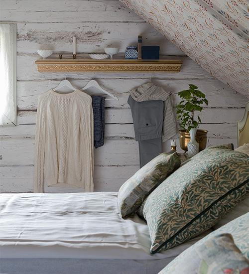 Kuddarna i sängarna är sydda med ett William Morristyg. På väggen agerar en kornisch med krokar, fyndad på loppis, klädhängare.