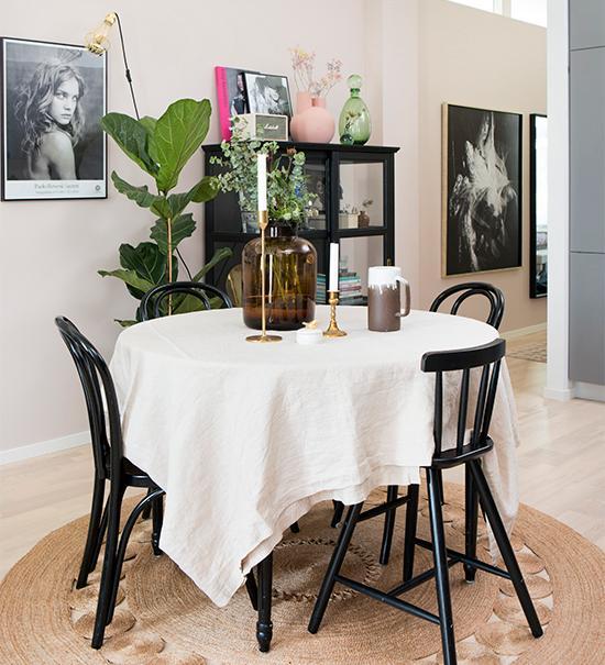 Matplatsen med bord i gustaviansk stil samt Ikeastolar, allt från Blocket, rund bastmatta, med genombrutet mönster från H&M home. Bordets placering i rummet ger utrymme för flera matgäster utan att det blir trångt. Väggens beigerosa färg valde Joy för att skapa en varm atmosfär, men också för att nyansen passar så bra till svarta möbler.