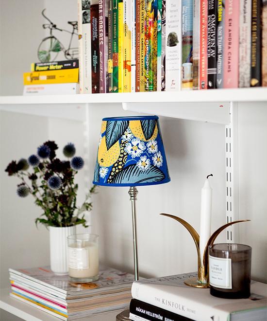 I vardagsrumshyllan står en lampa med skärm klädd i Josef Franktyg, köpt på Tradera. Torkade blommor från Hannas föräldrars trädgård och ljusstake från Skultuna.