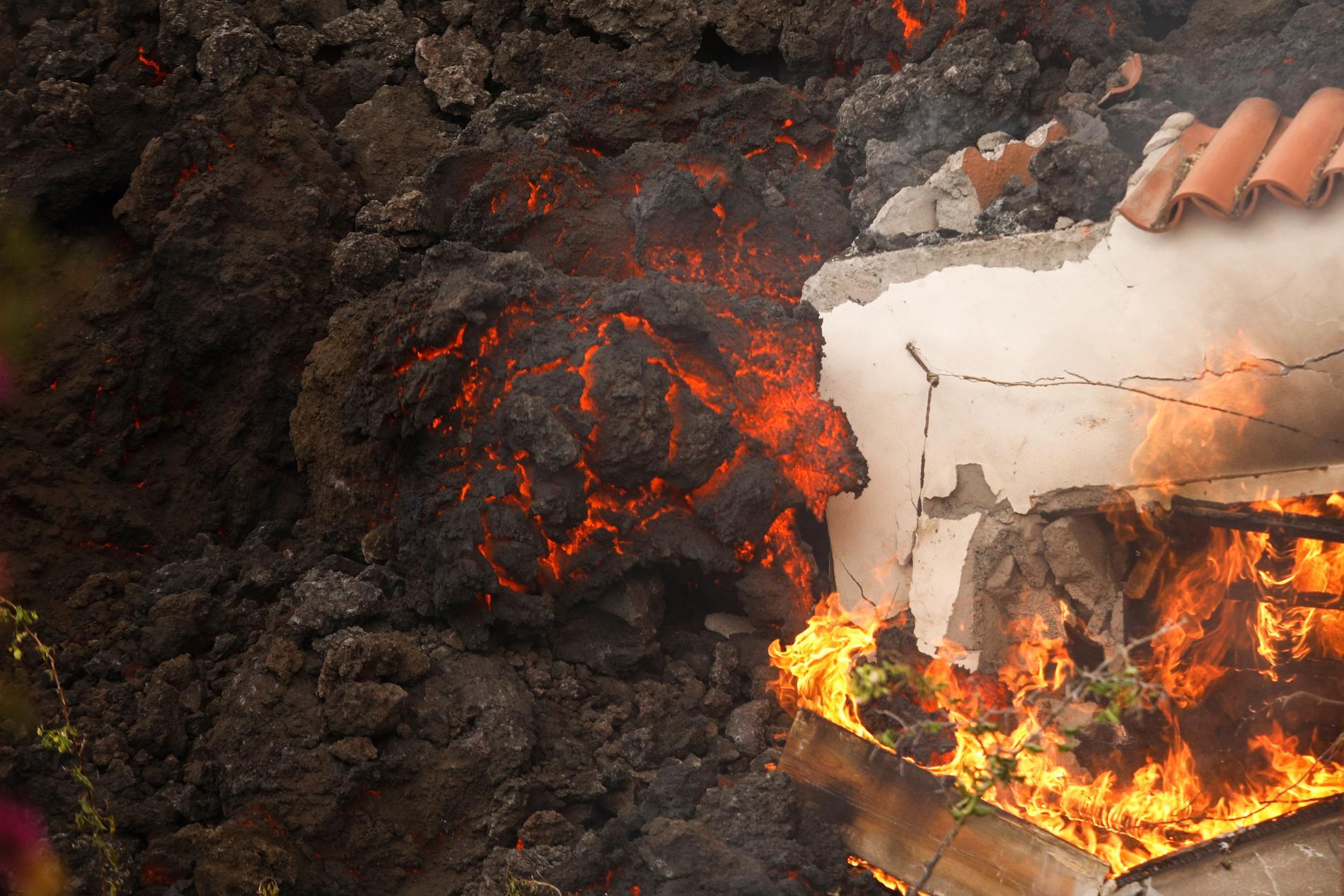 Rinnande lava slukar en byggnad nära El Paso på La Palma. Luften är fylld av svart rök. Tusentals människor har tvingats evakuera.