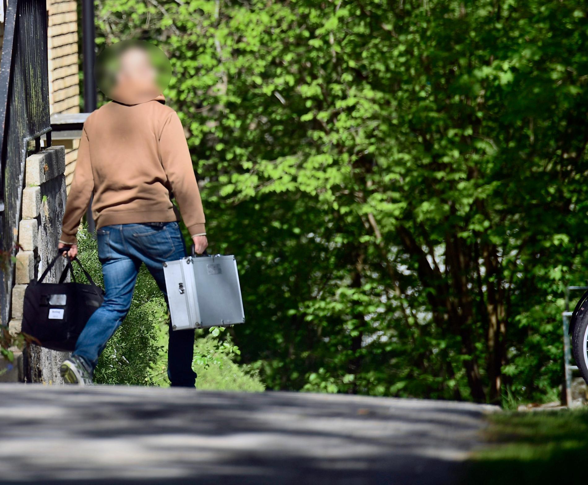 Civilklädd polis på en adress i nordvästra Stockholm efter genomförd razzia.