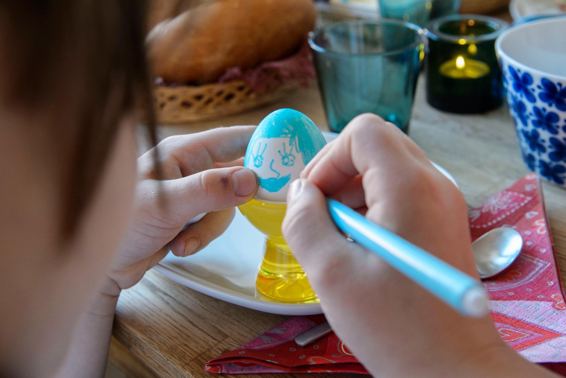 Ett påskpysslande barn målar ett ägg. Under påsklovet kan barn hämta pysselpåsar vid Konsthallen och vid vissa bibliotek.
