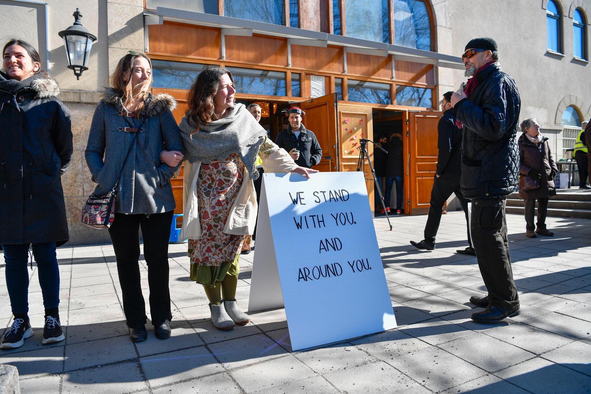 Linn Ahlbom och Fia Nerelius välkomnar en man till fredagsbönen, där stockholmare slagit en mänsklig ring kring moskén vid Medborgarplatsen i Stockholm.