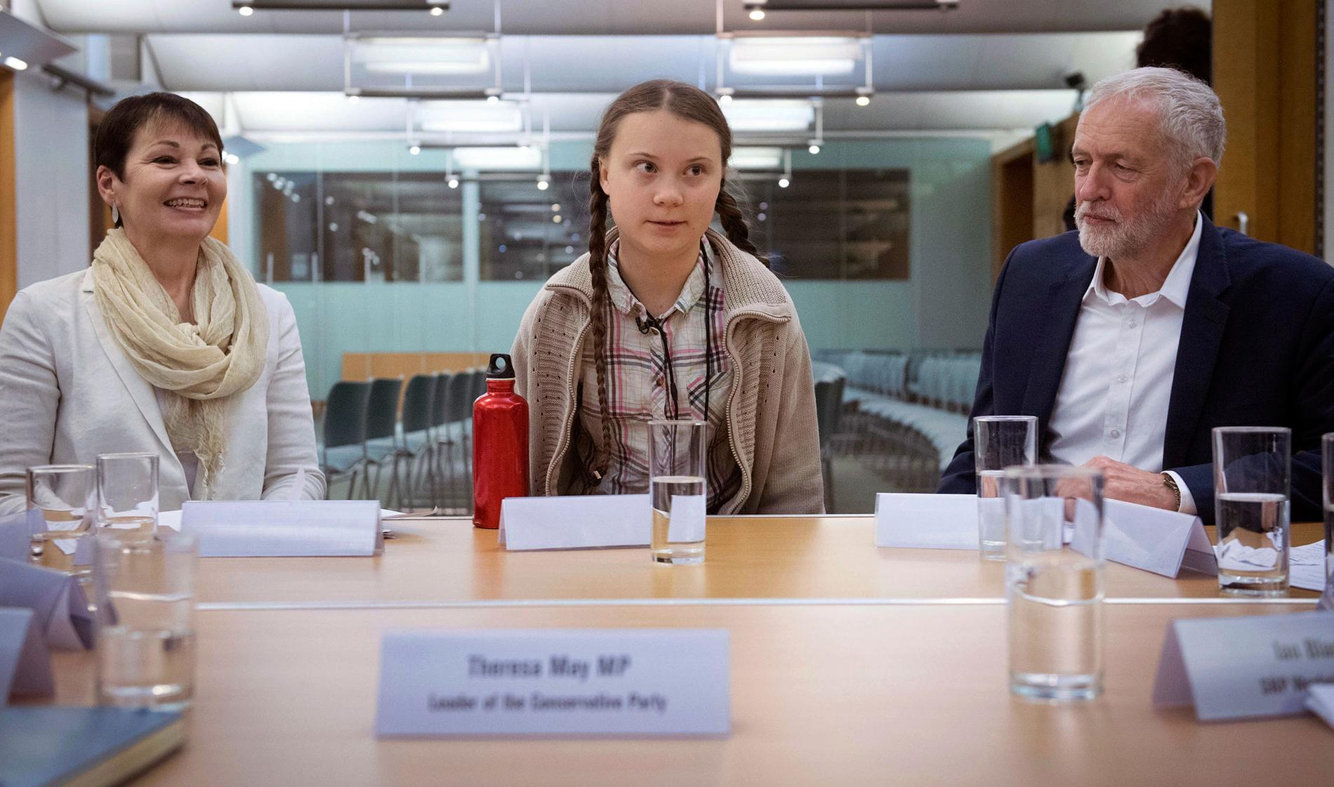 Greta Thunberg flankerad av Caroline Lucas och Jeremy Corbyn.