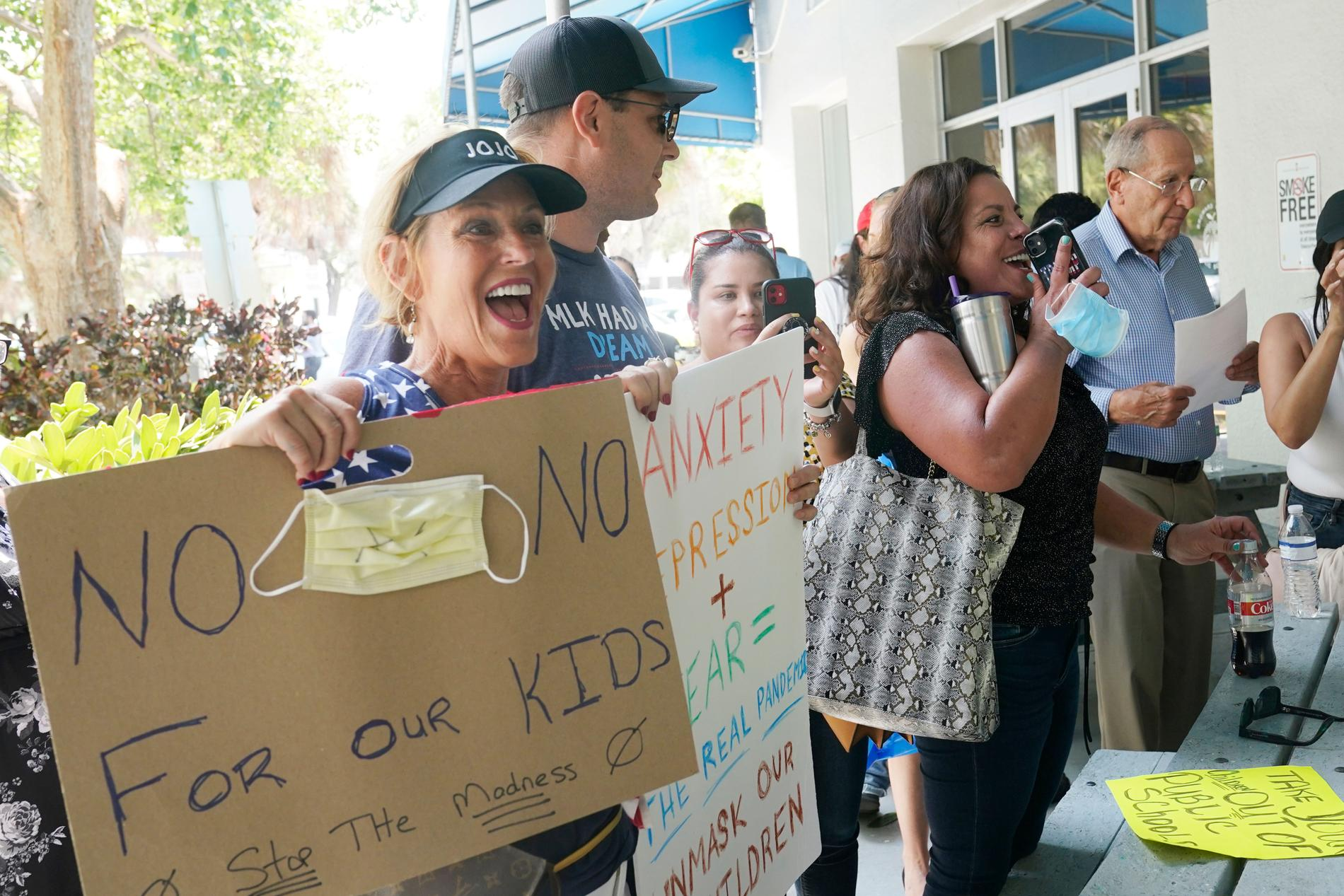 En liten grupp människor protesterar mot maskanvändandet på en skola i Florida och hävdar att deras barns personliga rättigheter kränks.