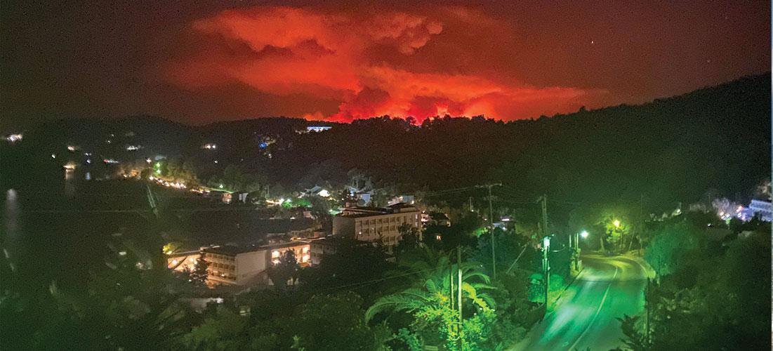 Ljuset från lågorna får den kraftiga brandröken att lysa röd på himlen över de grekiska öarna.