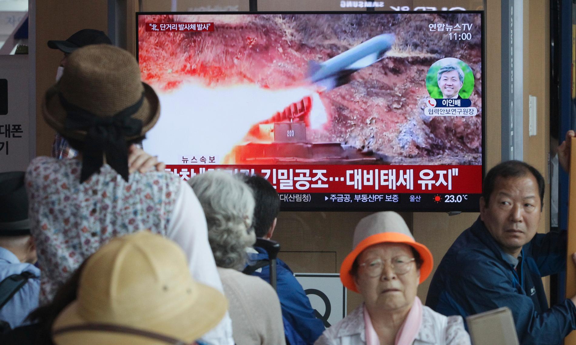 Människor i Seoul i Sydkorea tittar på tv-bilder på Nordkoreas robotuppskjutning.