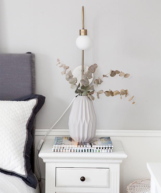 Vita detaljer i parets sovrum. Sängbordet är köpt på auktion. Vas och lampa från Mio.
