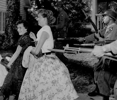Kvinnor som protesterat mot de svarta eleverna i Little Rock 1957 motas bort av militär.