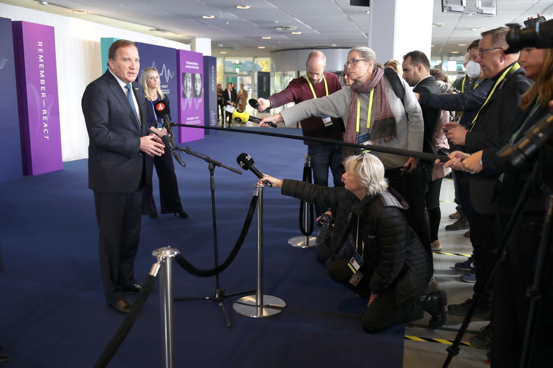 Stefan Löfven tar emot pressen på väg in på konferensen om antisemitism.
