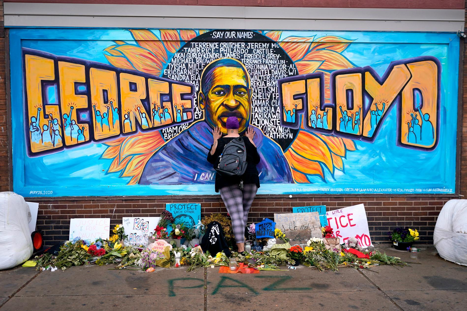 Förbipasserande hedrar George Floyd, som dog i ett våldsamt polisingripande i fjol, i dennes hemstad Minneapolis i USA. Där pågår nu en omröstning om huruvida poliskåren ska finnas kvar i sin nuvarande form.