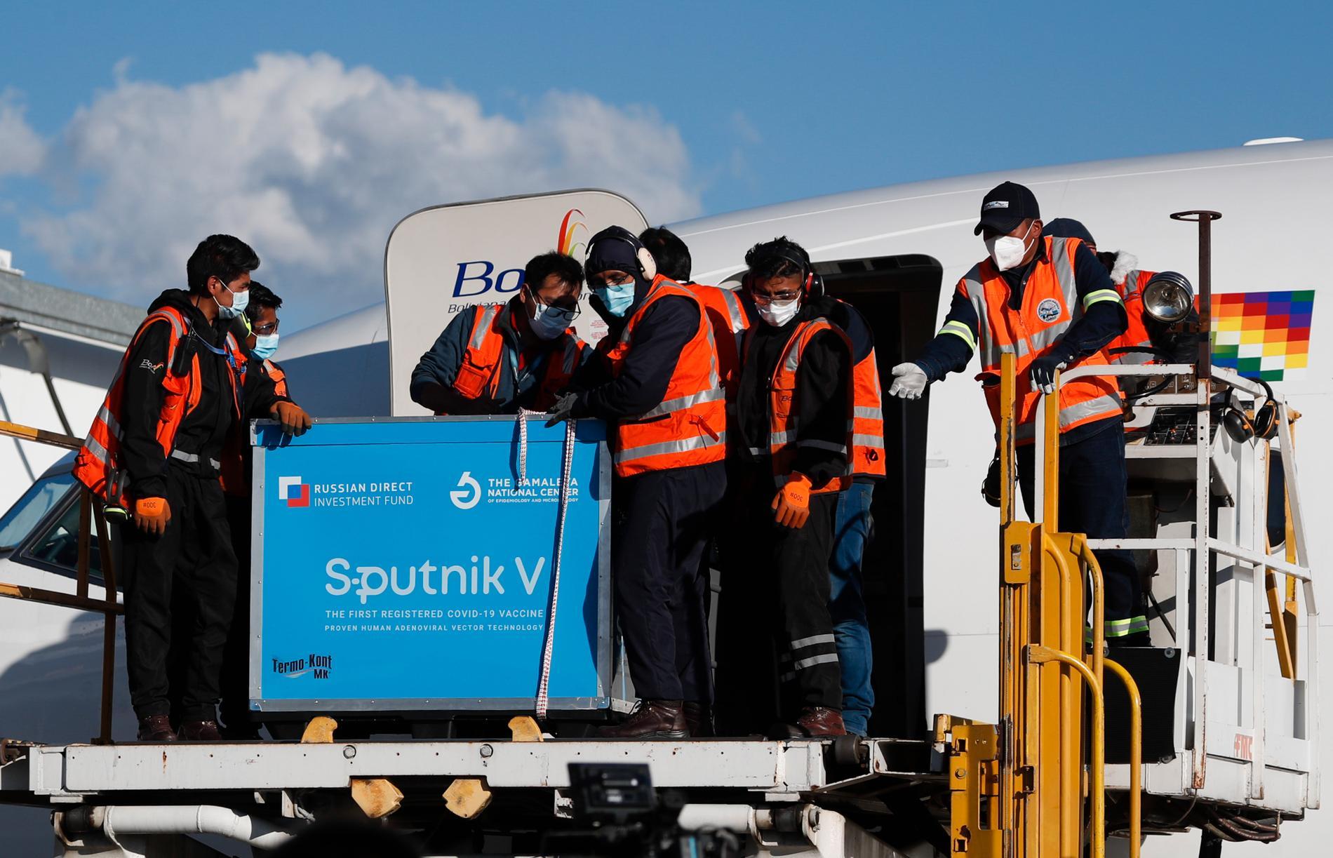 Flygplatspersonal i Bolivia tar emot landets första leverans av det ryska vaccinet Sputnik V.