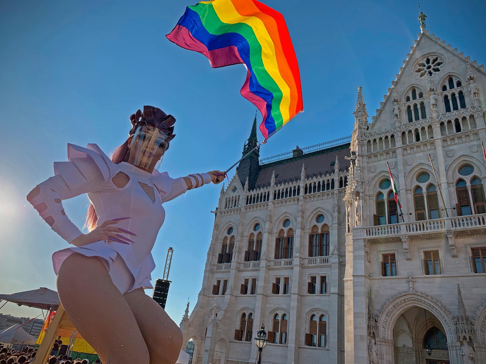 """En regnbågsflagga hålls upp i en protest utanför parlamentet i Budapest, som i tisdags godkände en omstridd ny lag som förbjuder """"främjandet av homosexualitet"""" i Ungern."""