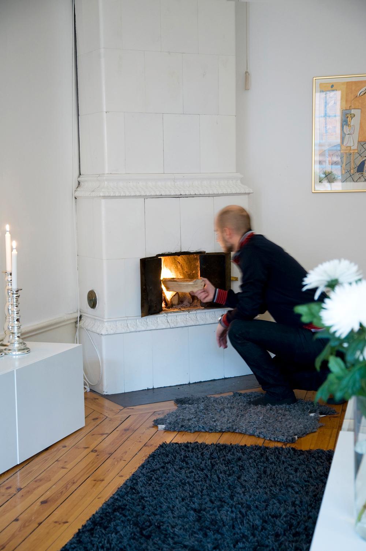 Johan eldar i en av de tre kakelugnarna, både för myskänslan och för att sprida värme i lägenheten.