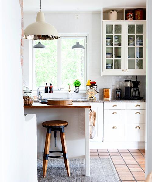 """Kök med lantlig känsla. Köksön Stenstorp är från Ikea och stolen från Huset brevé i Kungshamn. Köksvågen är köpt på loppis och kaffekokaren är en Moccamaster. Mattan är från Rusta. """"Plåtburken är en present från Fredriks far. Jag samlar på gamla plåtburkar"""", säger Victoria."""