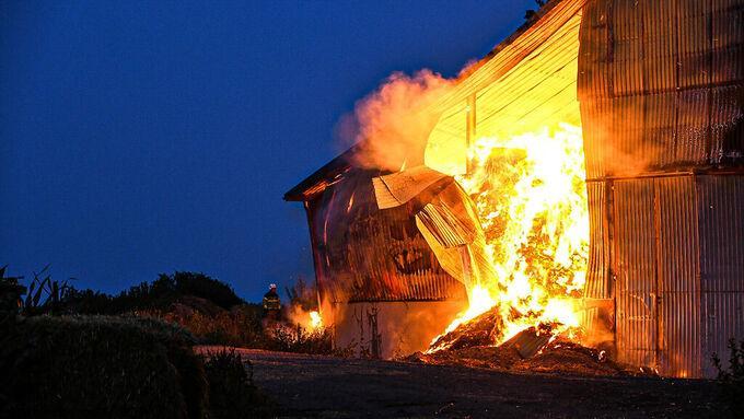 Två byggnader för halmlager brinner.