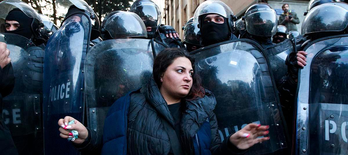 En kvinnlig demonstrant ställer sig framför polisen i samband med kravaller utanför parlamentsbyggnaden i Tbilisi i november.